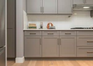 gray kitchen cabinets with brass fixtures