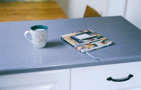 """cozy vibes"" coffee mug filled with milk and book on gray countertops"