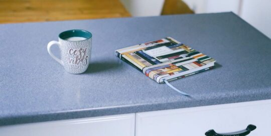 """""""cozy vibes"""" coffee mug filled with milk and book on gray countertops"""