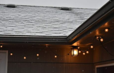 snow covered roof with hanging lights