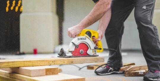 man cutting wood with dewalt circular aw