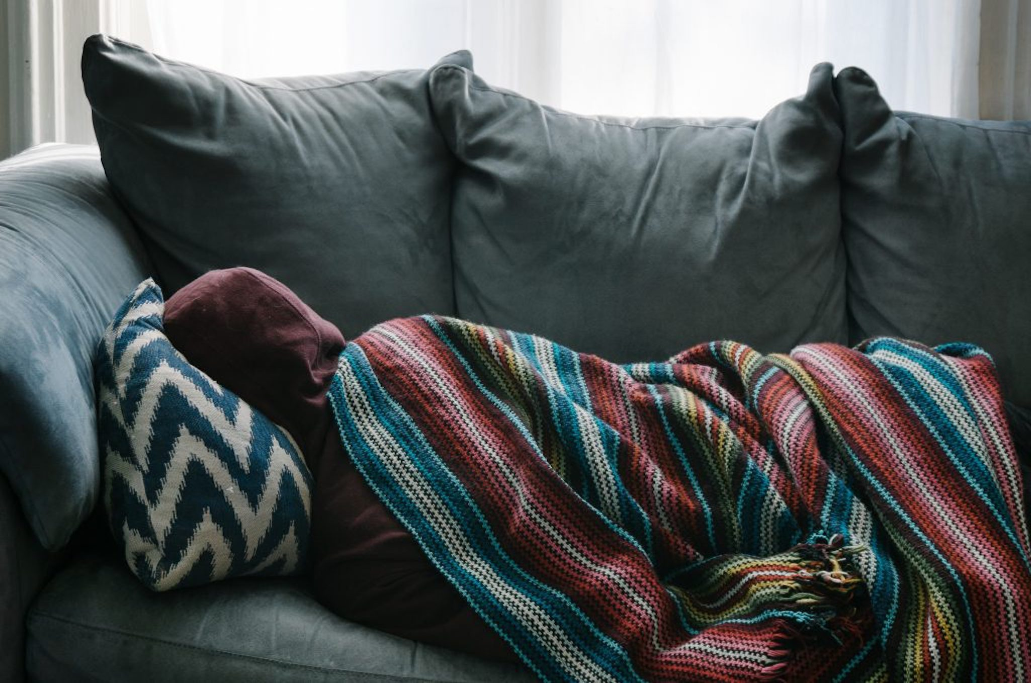 Person cold on sofa with blanket