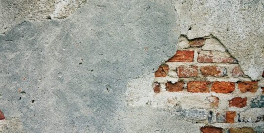 concrete wall with brick exposed in right corner