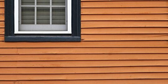 Orange siding with black framed window in left corner