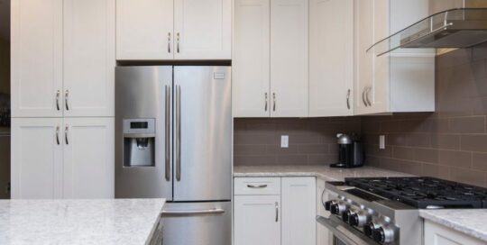 stainless steel appliances in white kitchen