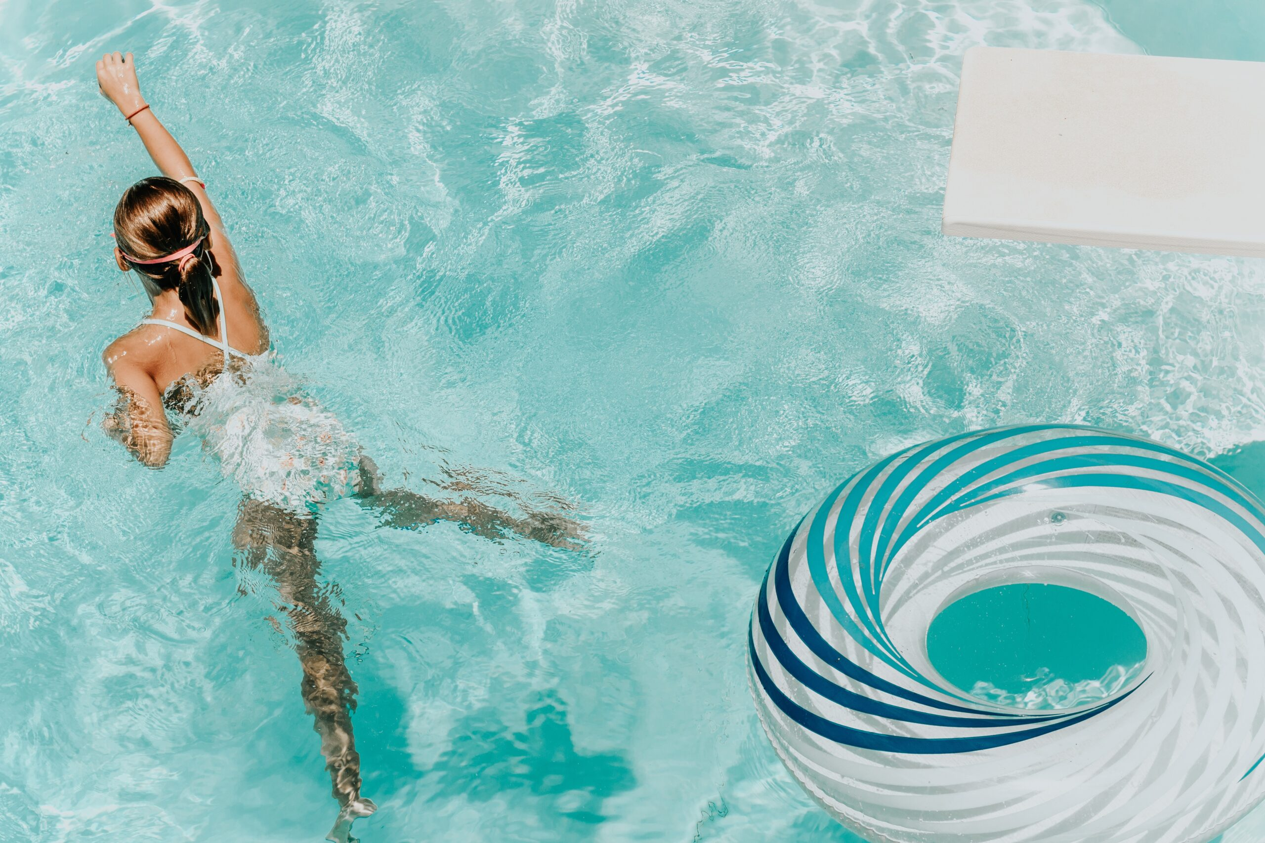 woman swimming in pool with float