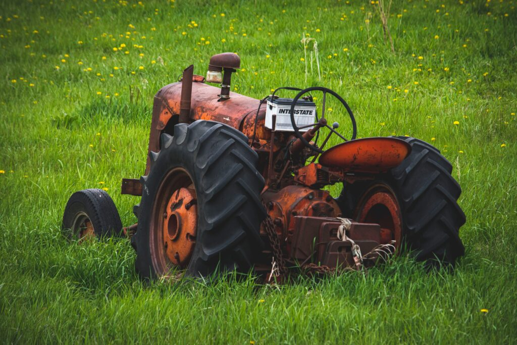 picture of antique red lawnmower sitting in a green field of grass