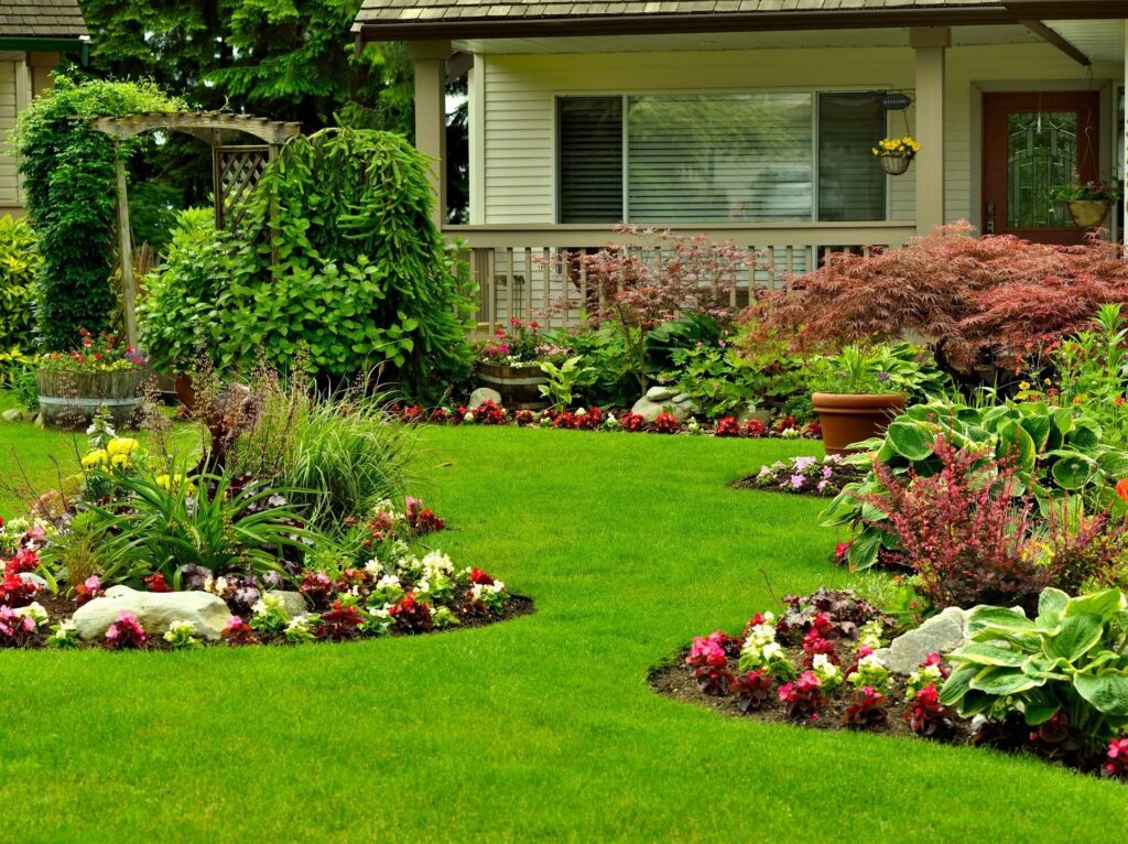 picture of green, lush, manicured lawn with flowerbeds