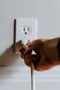someone unplugging an appliance from an outlet